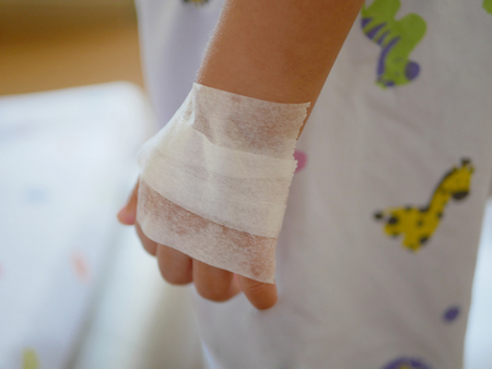 Little baby's hand covered with tape after applying cream for local anaesthesia, waiting to get numb before performing IV insertion Stock Photo
