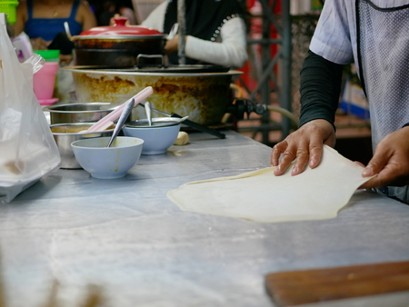 Roti dough being stretched and slapped into a sheet before being fried in hot griddle - delicious street food in Thailand