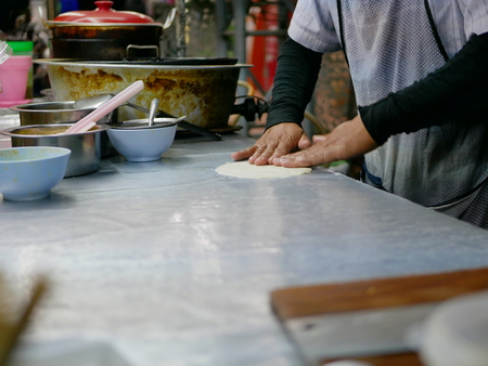 Roti dough being massaged and stretched into a sheet before being fried in hot griddle - delicious street food in Thailand
