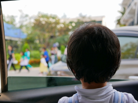Little Asian baby girl looking at a colorful parade through a car window - baby's curiosity 版權商用圖片