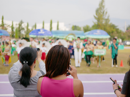 Asian mothers watching and taking photos of their children participating in a sport day event at school 版權商用圖片