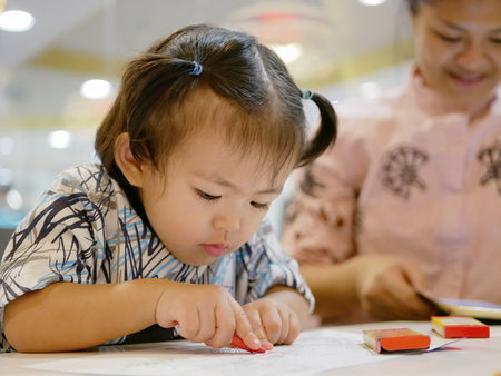 Little Asian baby girl being left alone with crayons, while her mother ignoring her and solely focusing on the smartphone