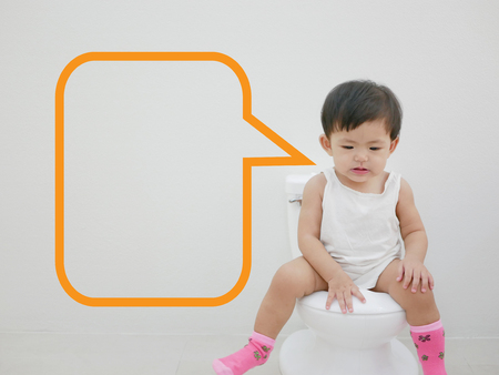 Adorable little Asian baby enjoys sitting on a baby-size toilet with a speech bubble ready to be filled