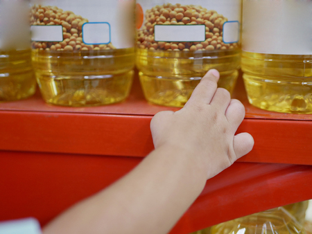 Little baby's hand picking / taking a bottle of cooking oil - getting baby involved / participated in shopping
