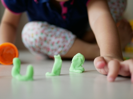 Playdough for baby being played on the house floor, promoting babys creativity, imagination, and fine motor skill development