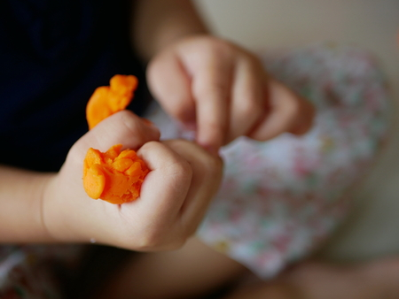 Close up of little baby's hands squeezing playdough - playing dough promotes baby's creativity, imagination, and fine motor skill development