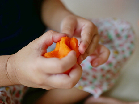 Close up of little baby's hands playing playdough - playing dough promotes baby's creativity, imagination, and fine motor skill development