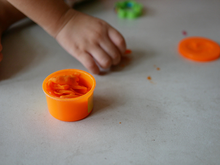 Little babys hands collecting and putting playdough back into the box, after finish playing