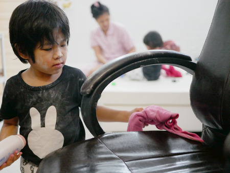 Little Asian baby girl cleaning her own mess, body powder, on leather chair - allowing baby to clean up their own mess to develop their sense of responsibility Imagens