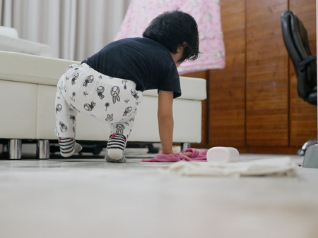 Little Asian baby girl cleaning her own mess, body powder, on the house floor - allowing baby to clean up their own mess to develop their sense of responsibility Stock Photo