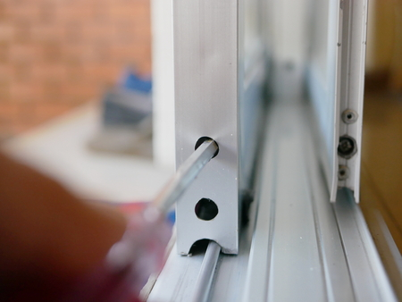 Close up of a screwdriver in a mans hand adjusting sliding glass door rollers