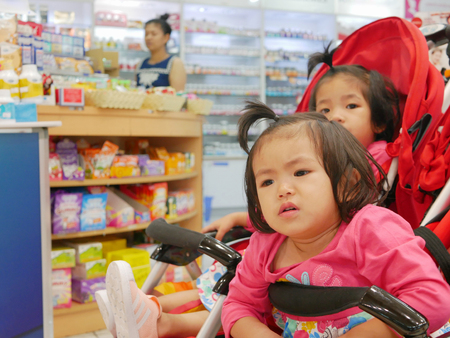 Little Asian baby girl (front), 22 months old, getting bored waiting for a long time in a baby stroller, with her older sister, for her mother buying drugs at a pharmacy 스톡 콘텐츠