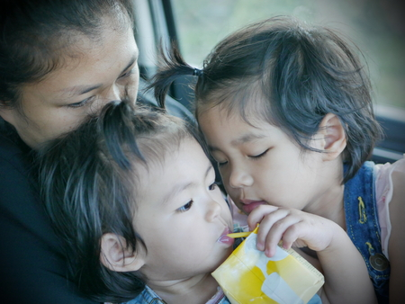 Selective focus of two little Asian baby girls, siblings, cuddling on her mothers lap in a car during a trip