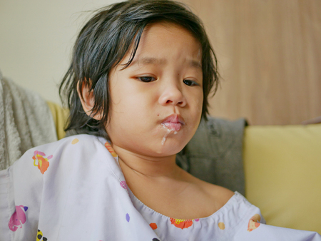 Close up of sick Asian baby girls lips getting pale and dirty with puke - vomiting in children and babies
