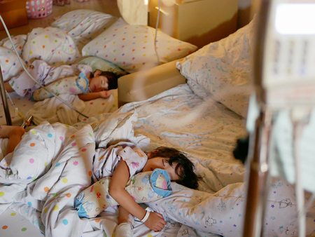 Selective focus of two sick Asian baby girls, siblings, were together admitted and staying in a hospital
