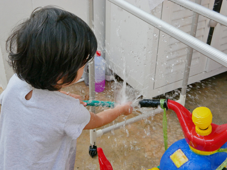 Little Asian baby girl playing water and learning to wash her plastic big bike