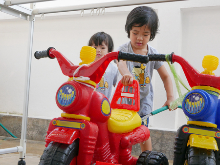 Little Asian baby girl learning to wash plastic big bikes while her little sister watching and standing nearby