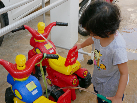 Little Asian baby girl learning to wash her plastic big bikes
