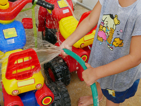 Little babys hands playing water and learning to wash plastic big bikes