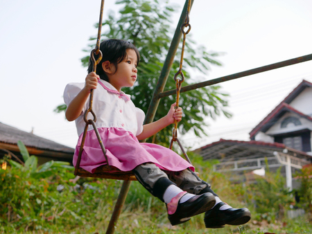 Little Asian baby girl riding a swing at a playground