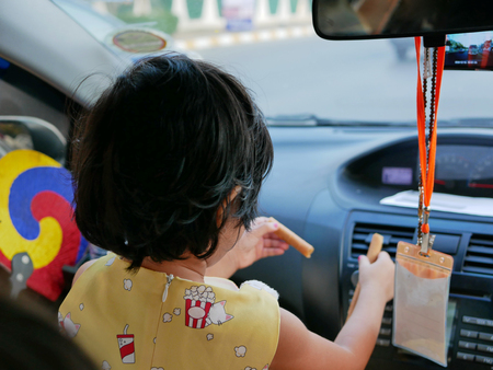 Little Asian baby girl, 38 months old, sitting and eating snack at the front seat of a driving car without fastening the safety belt properly