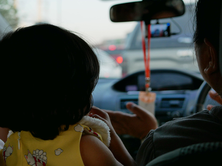 Little Asian baby girl, 23 months old, sitting between two front seats of a driving car, does not want to sit and fasten the safety belt properly on the rear seat