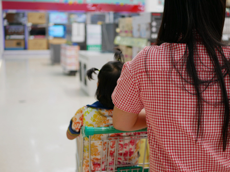 Selective focus of a mother doing shopping, pushing a shopping cart, with her little baby, daughter, inside