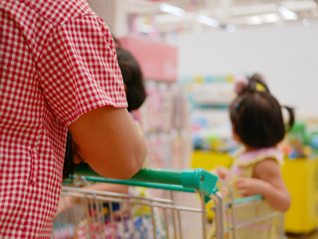 Selective focus of a mother doing shopping, pushing a shopping cart, with her two little daughters inside