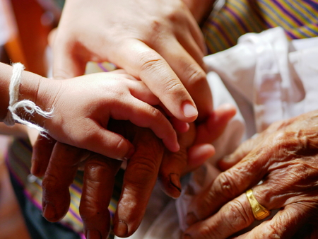 Hand of a woman on hands of her daughter and old mother - family bond