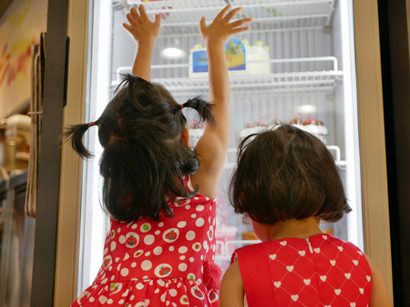Little Asian baby girls, sisters, looking and touching the bakery fridge as they were irresistibly hungry for beautiful cakes