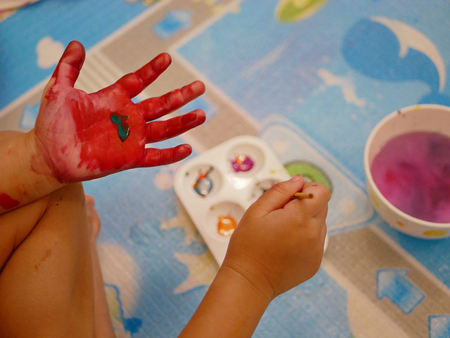 Hand of a little baby being painted with red and green colors - baby handprint / fingerprint painting 免版税图像