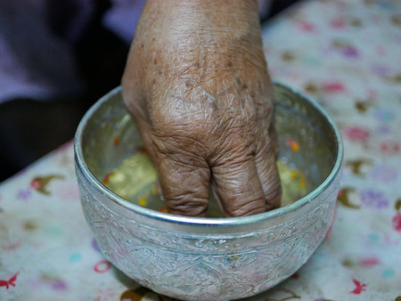 Selective focus of a hand of elderly person dipping into a cup ( salung ) filled with holy turmeric water before spraying the blessing water during Rod Nam Dam Hua ceremony, paying respect to the elders, in Songkran festival in Thailand