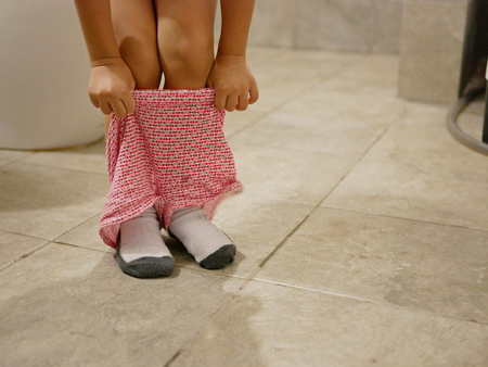 Selective focus of little baby's short pants being pulled up by herself after the baby finished using a toilet - potty trainning