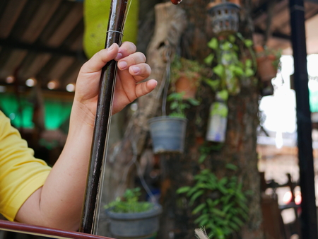 A musicians hand playing Salor, two or three-string spike fiddle used in the Lanna region or in the North of Thailand