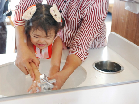 Mirror reflection of a little girl, with help from her mother, learning to wash her hands before a meal - teaching kids to wash their hands Imagens