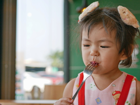 Little Asian baby girl enjoys tasting tomato ketchup by herself at a restaurant Stock Photo
