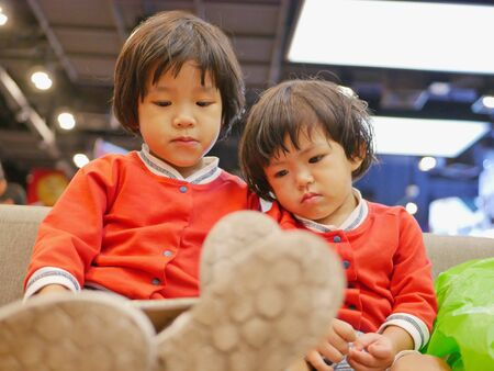 Two little Asian baby girl, sisters, sitting and watching a smartphone together, while waiting for her mother to do some errands - babies learned to share