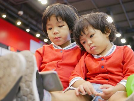 Two little Asian baby girl, sisters, sitting and watching a smartphone together, while waiting for her mother to do some errands - babies learned to share Banco de Imagens