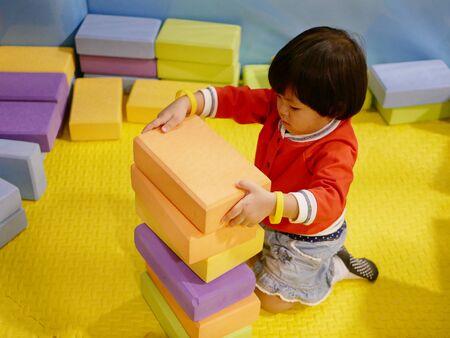 Pequeña niña asiática que apila ladrillos / bloques de espuma para construir en un patio de recreo interior: jugar con bloques de espuma ayuda a desarrollar la motricidad fina y las habilidades de pensamiento lógico de los niños