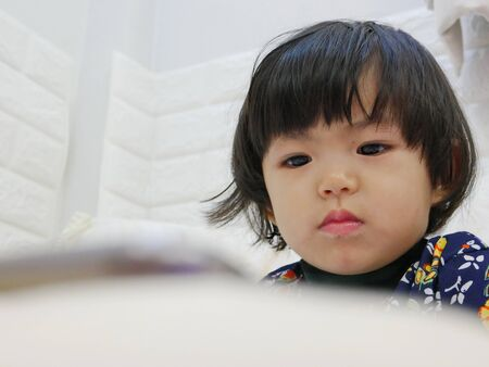 Little baby girl's face, 2 years old, while watching / staring at a smartphone