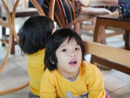 Little Asian baby girl sitting and playing / exploring with her younger sister under a dinning table at a restaurant - toddler behaviours at mealtime