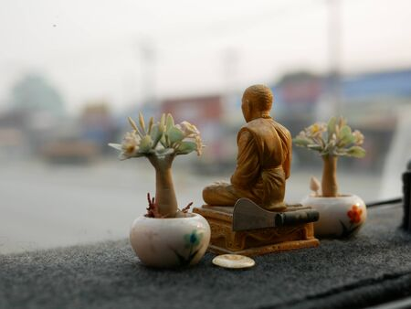 Close up of a monk statue being placed on a driving car dashboard in Thailand as the Thais believe that the statue, being holy, can save them from road accident