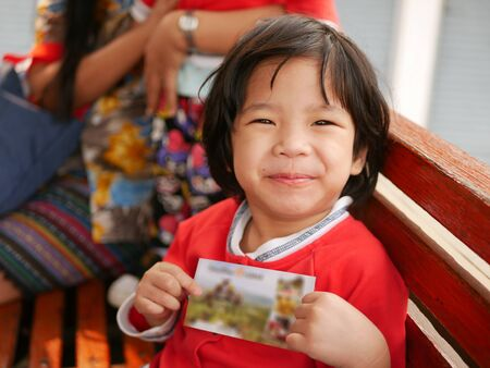 Little Asian baby girl, 29 months old, very happy getting a ticket to visit a sightseeing with her mother - take your kid out to explore new experience