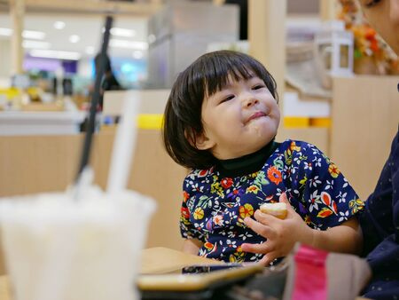 Little Asian baby girl, 24 months old, enjoys having a piece of butter bread with whipped cream by herself at a shopping mall Фото со стока