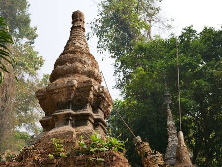 Old grungy small pagoda ( chedi ) abandoned in a forest - Buddhist religious architecture