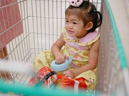 Little Asian baby girl sits in a cart, enjoys doing shopping with her mother - doing errands with toddler