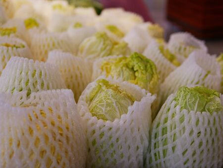 Selective focus of fresh cabaged covered with foam mesh wrap for sale in a supermarket - buying vegetables / healthy choice Stok Fotoğraf - 129808060