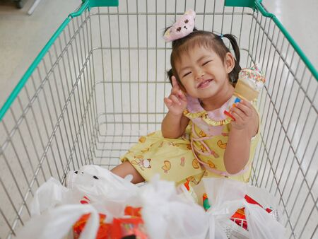 Little Asian baby girl enjoys eating ice cream cone in a cart, while waiting for her mother to do shopping at a supermarket