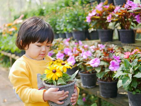 Happy little Asian baby girl receiving  taking a pot of refreshing yellow flowers from her mother - engaging with nature provides positive impact on childrens health and development Stock fotó