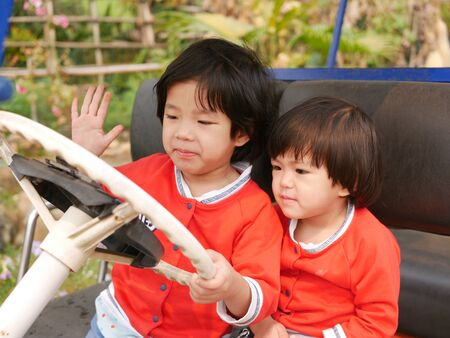Two ittle Asian baby girls, sisters, holding on a steering wheel and pretending to drive a parking car - pretend play enhances the babys development